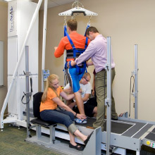 3 people helping adjust a harness holding anotther person on a treadmill